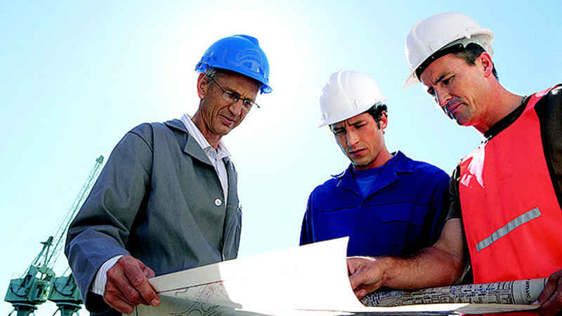 Three construction men are standing and viewing a set of blue prints with a large crane in the foreground.